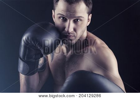 Boxing concept. Boxer with an aggressive look in boxing gloves before a fight on a black background