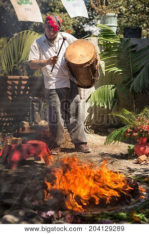 January 31 2015 San Pedro la Laguna Guatemala: Mayan man beating a drum during shamanic ritual next to fire