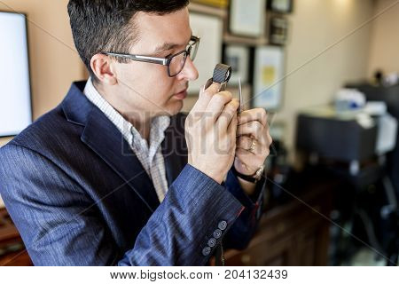 Jeweler Looking At Diamond Through Loupe
