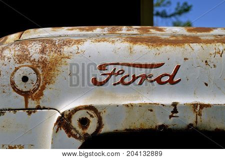 BARNESVILLE, MINNESOTA, June 19,  2016: The rusty Ford tractor hood logo is a product of the Ford Motor Company located in Dearborn, Michigan started by Henry Ford and incorporated on June 16, 1903.