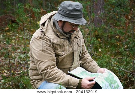 Hiker with map in forest .boondocks -taiga