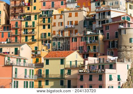 Picturesque view of the colorful houses along the main street in a sunny day in Manarola. Manarola is one of the five famous villages in Cinque Terre (Five lands) National Park. Liguria, Italy, Europe