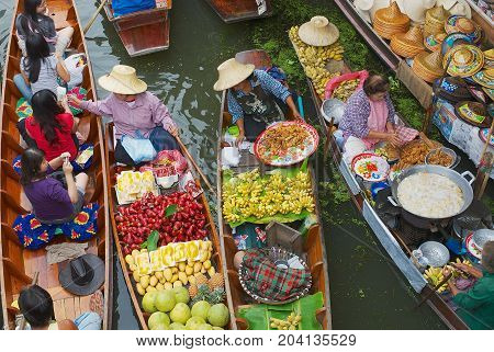 DAMNOEN SADUAK, THAILAND - MAY 15, 2008: Unidentified women sell food from boats at the floating market in Damnoen Saduak, Thailand.