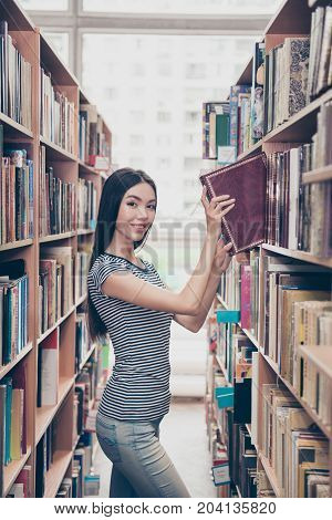Young attractive clever successful asian female student is putting vocabulary on the book shelf smiling so skinny wearing casual striped t shirt behind her are book shelves of campus library