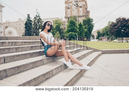 Attractive Carefree Gorgeous Lady With Bronze Skin Is Posing In Town, On Stroll, Sitting On Concrete