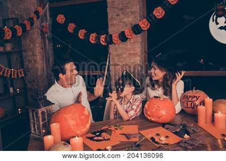 Three cheerful relatives - frightened dad boy in carnival eyewear and pirate cap mommy in wizard headwear carved pumpkins around candles with flame spooky dark room indoors at home