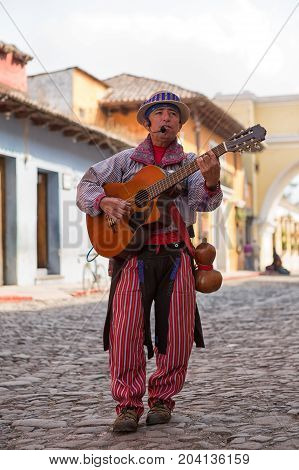 February 8 2015 Antigua Guatemala: man in traditional clothing playing guitar on the street