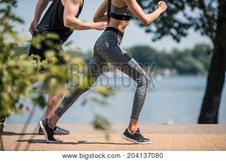 partial view of sportive couple jogging together in park