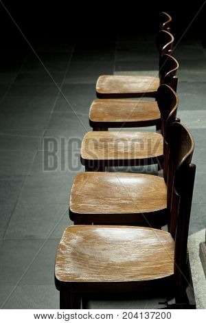 row of empty vintage brown wooden chairs