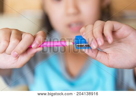 Little girl sharpening a pencil.Hands sharpening pencil