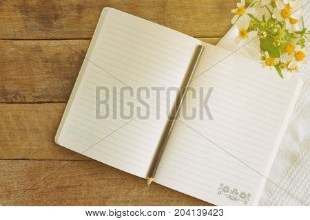 White notebook open on rustic wood table with pencil in top view flat lay. Notebook open on desk with pencil and vase of chamomile so freshness and relax.Copy space concept for background or wallpaper. Notebook on table for business concept