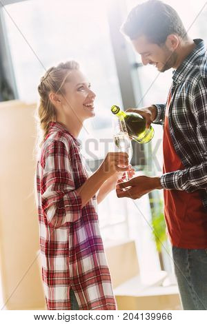 happy young couple couple drinking champagne in new apartment