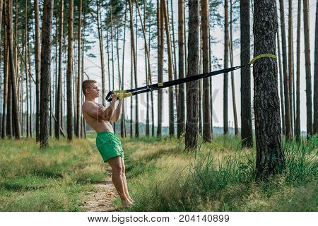 Male athlete excellent training trx, fresh air in nature in the summer in the park, feel your strength, motivation, full-length. Exercise of the biceps muscles. A sunny day. Stamina of a man. Against the background of trees.