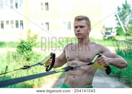 Male athlete is an excellent trx training, fresh air in nature in the summer in the city, feel your will power of balance, motivation, close-up. Exercise of the muscle of the chest. The pumped press. Stamina of a man.