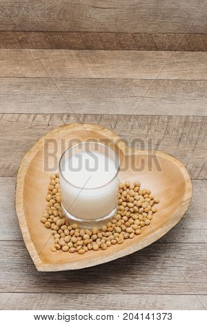 Glass with soy milk and soy bean on wooden heart shape plate