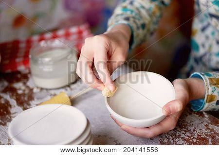 Master ceramist rubs a plate of baked clay. A creative workshop.