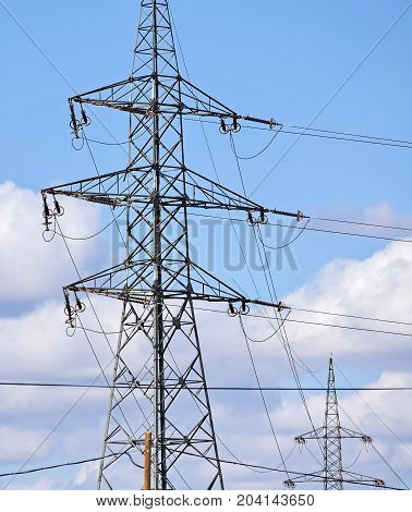Electricity pylons against blue cloudy sky and clouds