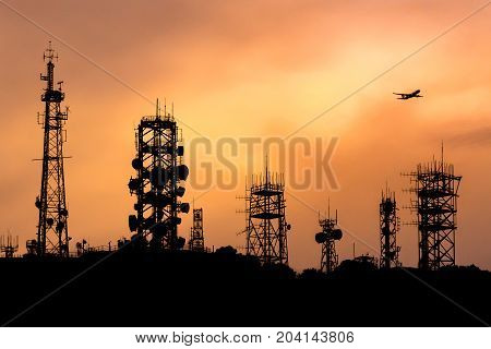 Silhouette of communication towers on mountain with airplane above