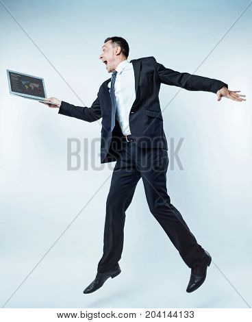 Hurray. Very emotional mature man in a black suit cannot stand on one place and jumping high while looking at a screen of his laptop with a wide opened mouth.