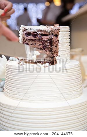 White wedding cake sliced open with cholate and black cherry filling