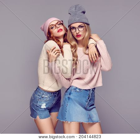 Fashion. Young Beautiful woman in Stylish Autumn outfit Hugging. Pretty Sisters Best Friends Twins. Hipster Blond Redhead Model, fashion Cozy jumper, Glasses. Girls in Trendy Beanie hat.Vanilla color
