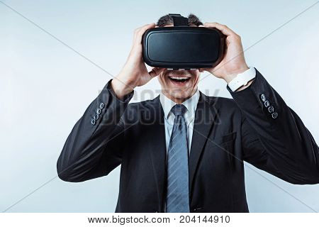 Unreal feeling. Waist up shot of a joyful businessman using a VR glasses getting excited while standing over the background with his mouth wide opened.