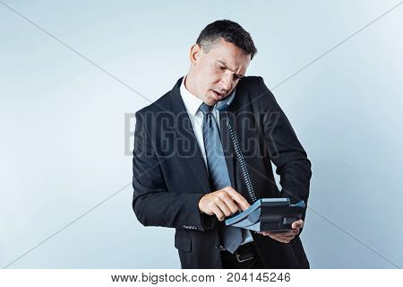 Serious issue. Worried man of business wearing a black suit holding an office telephone while trying to make a business call over the light background.