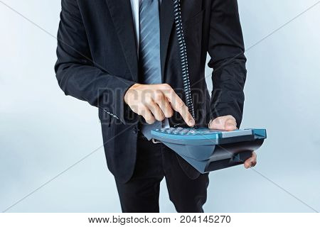 Business is calling. Scaled up look on a male employee wearing a black suit pressing a number button on an office telephone while making a business call.