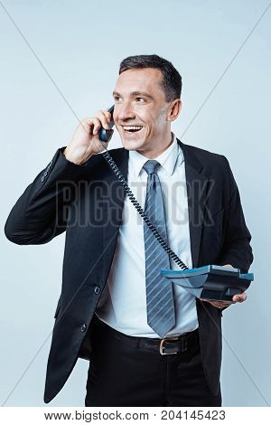 How are you. Cheerful mature gentleman in a black suit grinning broadly while listening to somebody on a telephone and enjoying the conversation.