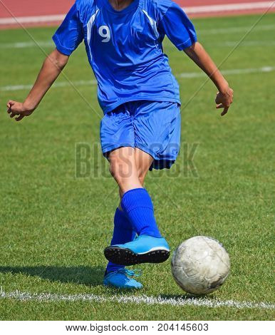 Young soccer player kick off the ball