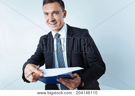 Loving my job. Radiant man wearing a black suit looking into the camera with a broad smile o his face while posing with notes on a clipboard over the background.