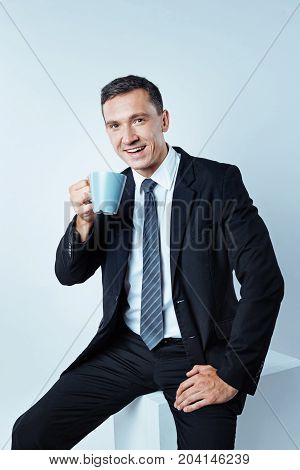 Time to relax. Cropped shot of a mature entrepreneur wearing a black suit looking into the camera and smiling while recharging his batteries with a cup of aromatic coffee.