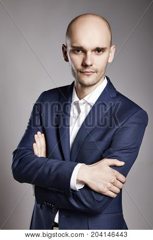 Portrait of young pensive businessman looking at camera.
