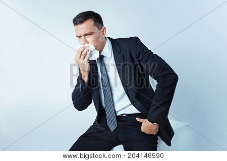 Caught an illness. Chopped shot of a bit confused man sitting on a studio cube and using a paper napkin while wanting to sneeze hard.