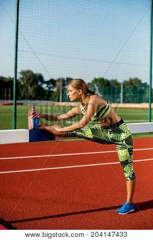 Young, beautiful girl athlete in sportswear doing warm-up at the stadium. Outdoor stadium
