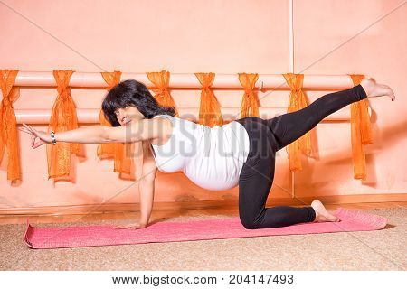 Pregnancy Yoga and Fitness concept. Healthy maternity lifestyle concept. 40 week pregnant middle aged caucasian woman on the knee in asana doing yoga exercise virabhadrasana.