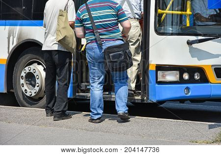 People getting in to the bus in the city