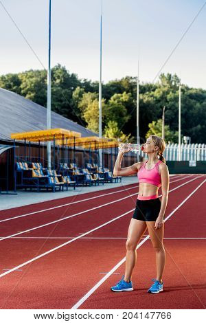 A young girl who participates in sport at the stadium drinking water. Sport background. Outdoor stadium