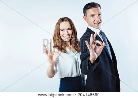Very good. Waist up shot of female and male working people standing next to each other and showing an okay sign while both posing over the background.