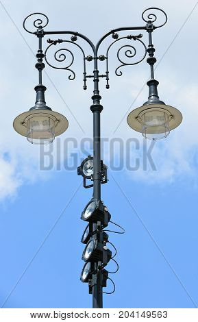 Ornate street lights with reflectors in summer