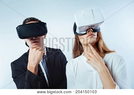 Let me think. Thoughtful colleagues standing next to each other and dreaming while both wearing a 3D visual reality headsets over the background.