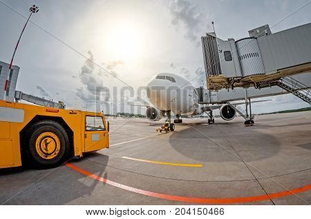 Parking At The Airport An Airplane At The Teletrap And An Airfield Tractor, Ready For Departure To T