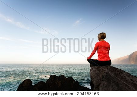 Woman meditating in yoga pose ocean view beach and rock mountains. Motivation and inspirational fit and exercising. Healthy lifestyle outdoors in nature concept.