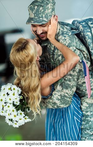 wife meeting husband in military uniform at airport