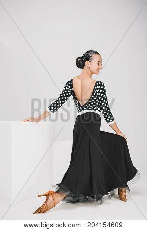 cute woman in black dress in studio, dancer posing and smiling