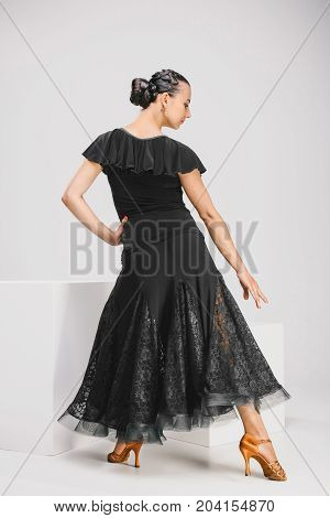 pretty woman in black dress in studio, nice dancer turning backwards
