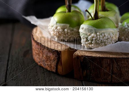Apples in white chocolate coating with sticks. Dessert for Halloween