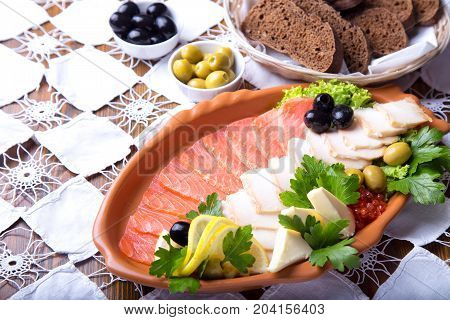 Seafood platter with salmon slice and halibut, decorated with olives and lemon on wooden background. Mediterranean appetizers.