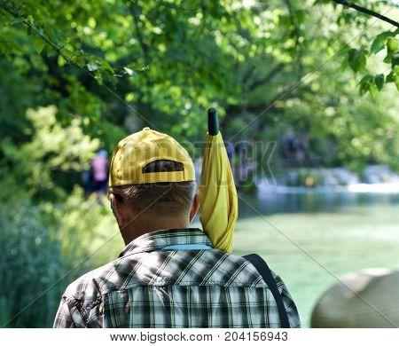 man with a yellow cap und a yellow umbrella