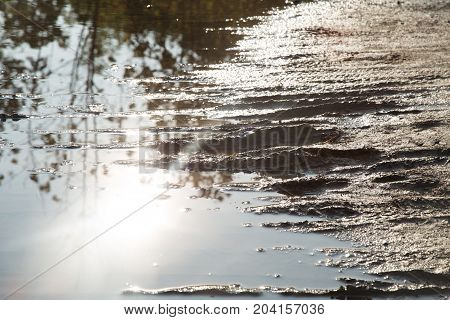 Dirt pool with traces from wheels on the road after a rain. Wet ground surface